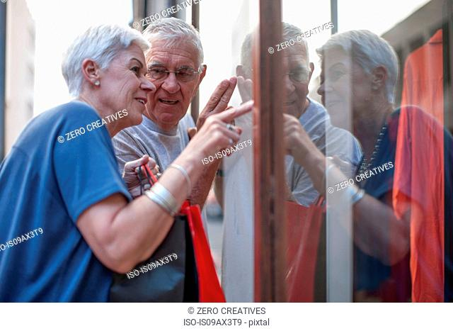 Senior couple pointing at city shop window