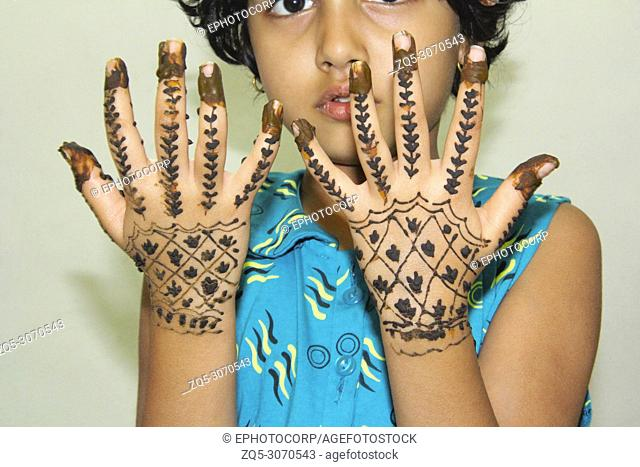 Little girl showing mehendi or tattoo drawn on her hand