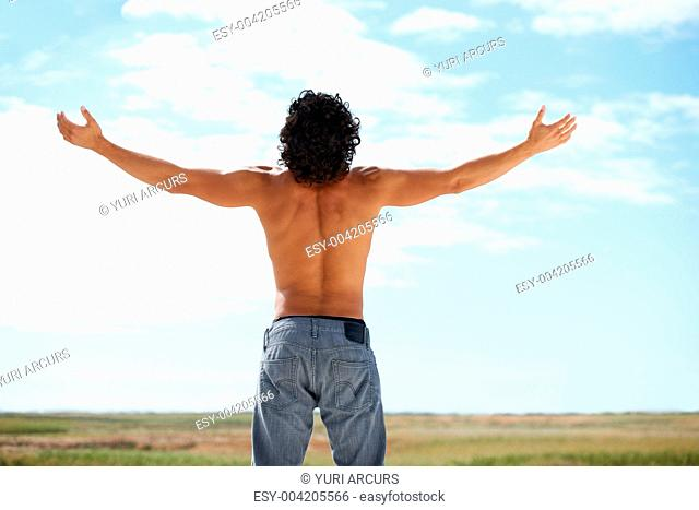 Rearview of young man wearing no shirt raising his arms to the sky
