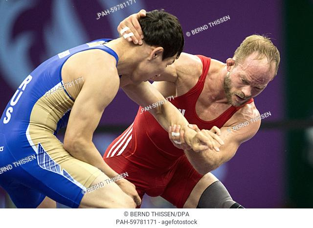 Germany's Marcel Ewald (red) competes with Viktor Lebedev (blue) of Russia in the wrestling Men's 57kg Freestyle Finale at the Baku 2015 European Games in the...