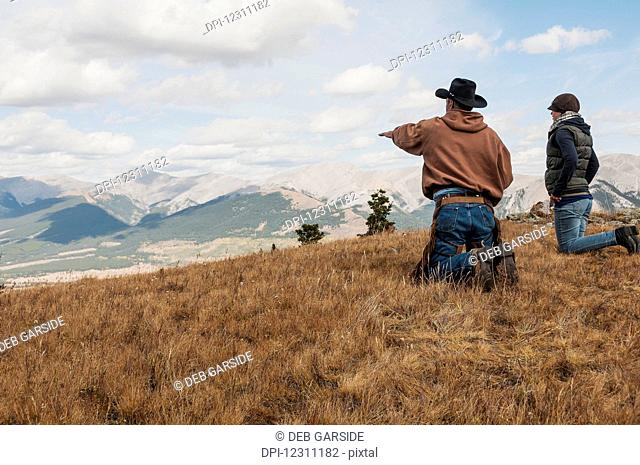 Cowboy and a female on their knees looking out towards the rocky mountains, Ya-Ha-Tinda Ranch; Alberta, Canada