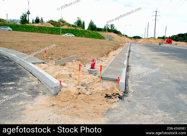 building new road construction site cars going roundabout and lighting pole wires lay