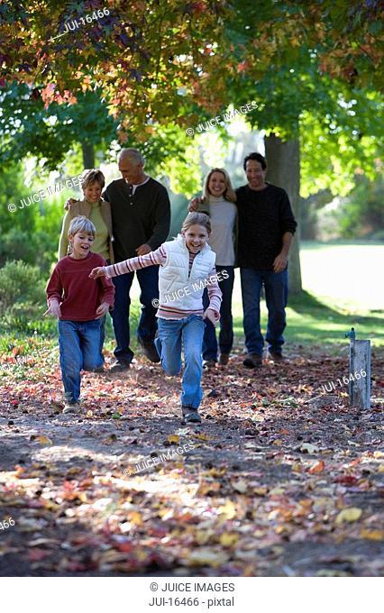 Multi-generational family walking in park in autumn