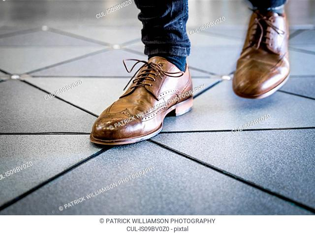 Feet in pair of brogues on tiled flooring