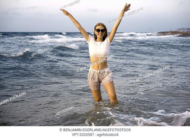 young woman at beach wearing wet clothes while standing in sea water, in Crete, Greece