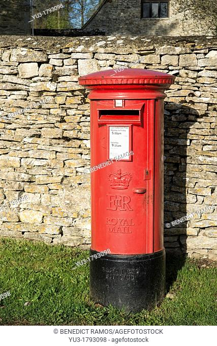 Red postbox by a drystone wall Tackley Oxfordshire England UK