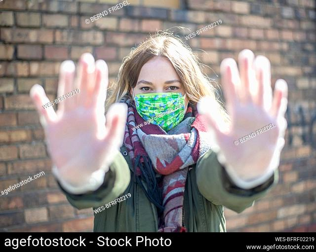 Portrait of young woman wearing mask raising her hands