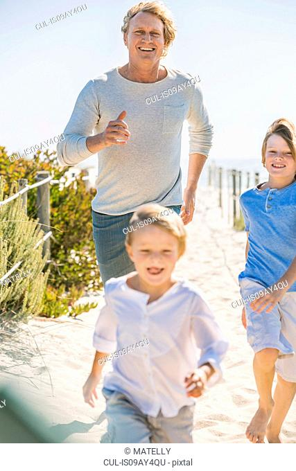 Father and children running on beach