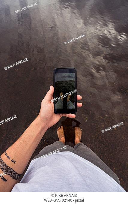 Man taking a cell phone picture with feet in water of a lake
