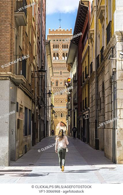 A tourist walks along the streets of Teruel. Saint Martin's tower in Background. Teruel, Aragon, Spain, Europe