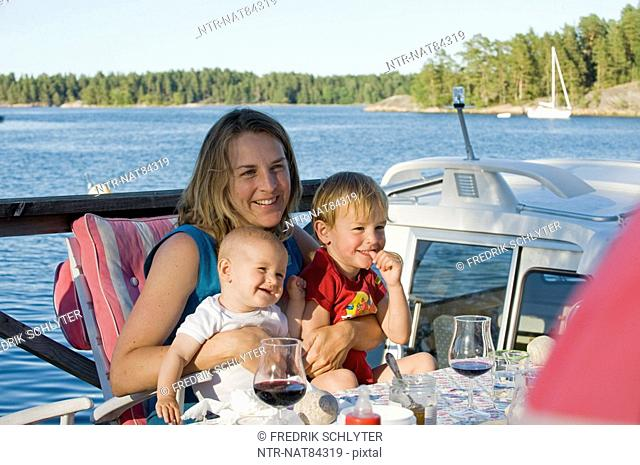 Woman with two children eating outdoors, Sweden