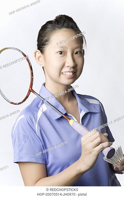 Portrait of a young woman holding a badminton racket and a shuttlecock