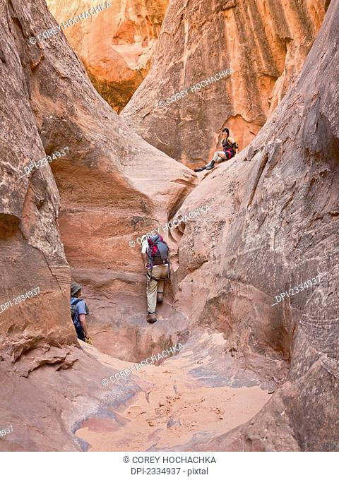 People exploring a slot canyon;Hanksville utah united states of america