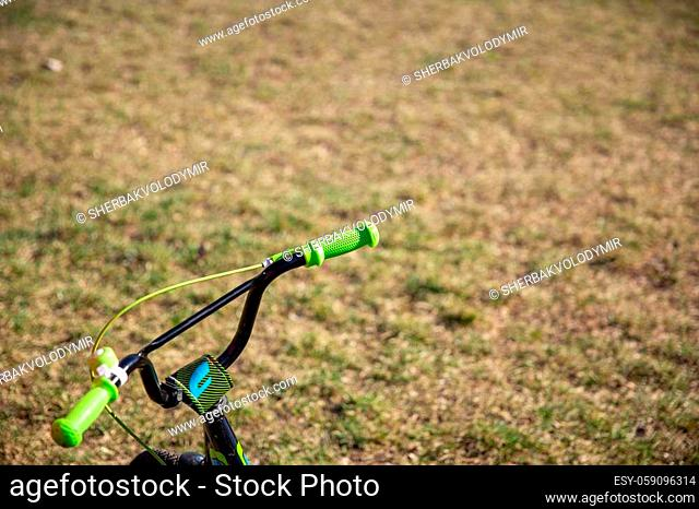 Small children's bike in the park. children's bicycle steering wheel on grass background. Space for text