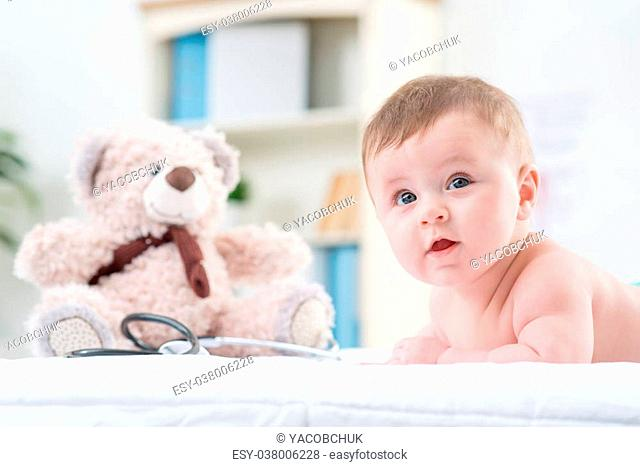Full if curiosity. Positive expressive cute little infant lying on the couch in the hospital while looking aside