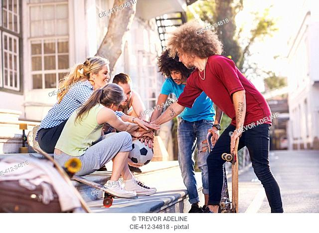 Friends with soccer ball and skateboards touching hands in huddle on urban steps