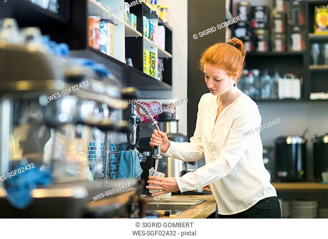 Young woman working in coffee shop, washing dishes