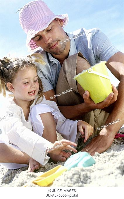 View of a father and daughter playing in the sand