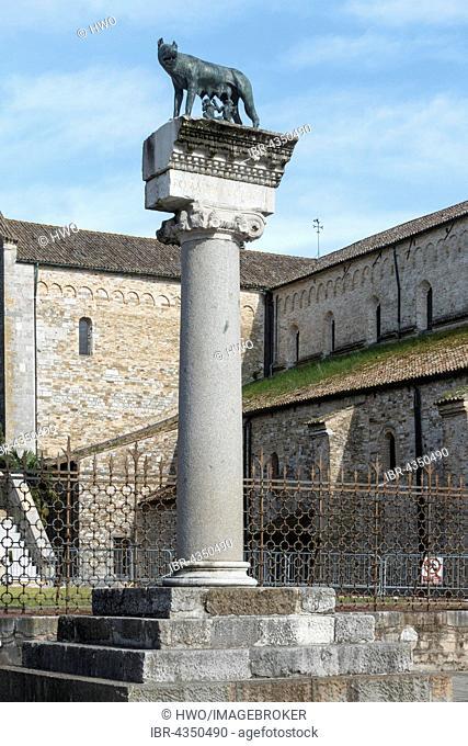 Roman column with Capitoline wolf, behind Romanesque basilica, Aquileia, Udine province, Friuli-Venezia Giulia, Italy