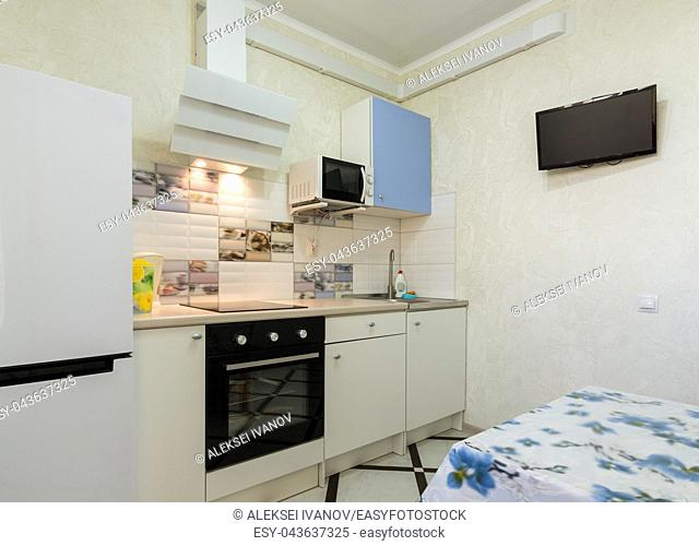 The interior of a small kitchen with a TV on the wall
