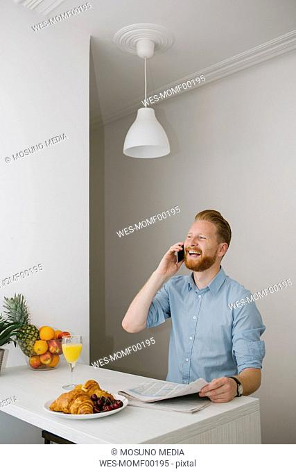 Laughing businessman on the phone at breakfast table at home