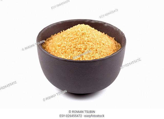 brown sugar in a dark bowl with wooden spoon isolated on white