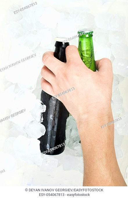 Hand holding bottle of beer and ice cubes