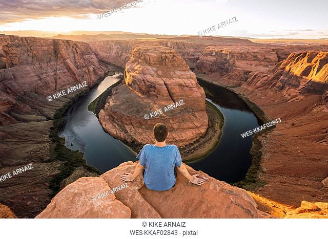 USA, Arizona, Colorado River, Horseshoe Bend, young man sitting on viewpoint