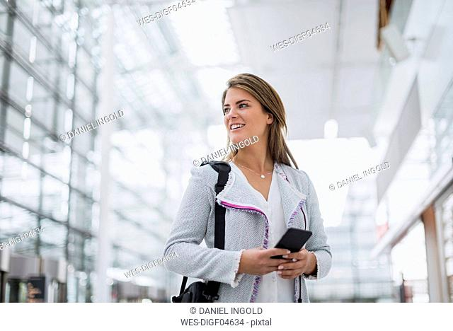Portrait of smiling young businesswoman with cell phone at the airport looking around
