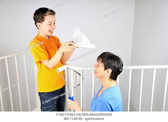 Paintwork, boy putting a paper hat on his mother's head
