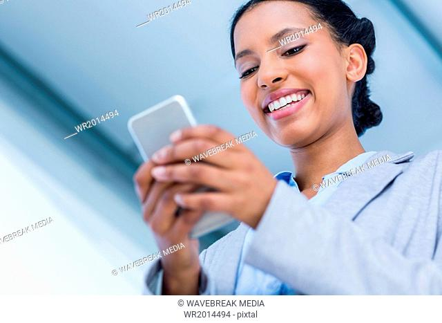 Happy businesswoman using her smartphone