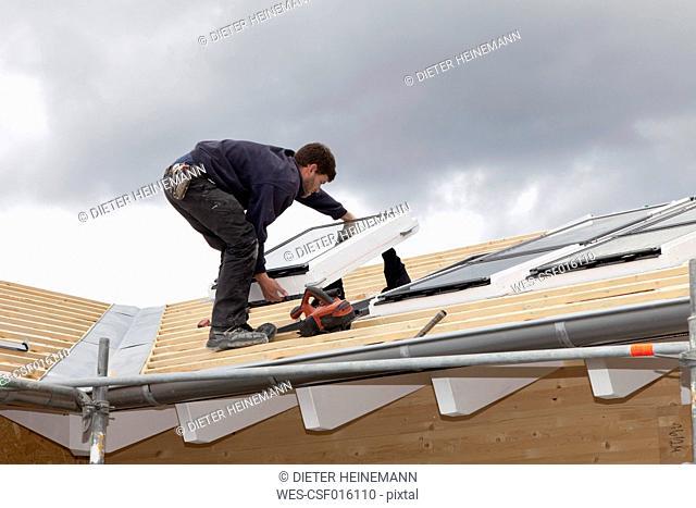 Europe, Germany, Rhineland Palatinate, Worker installing roof windows
