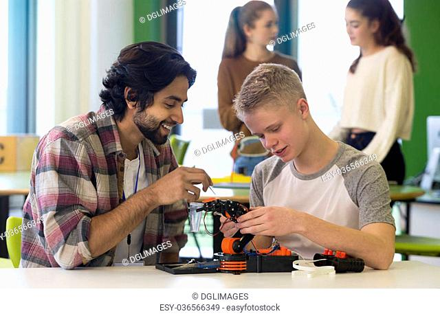 Student and teacher working on a robotic arm in a classroom. There are students standing in the background