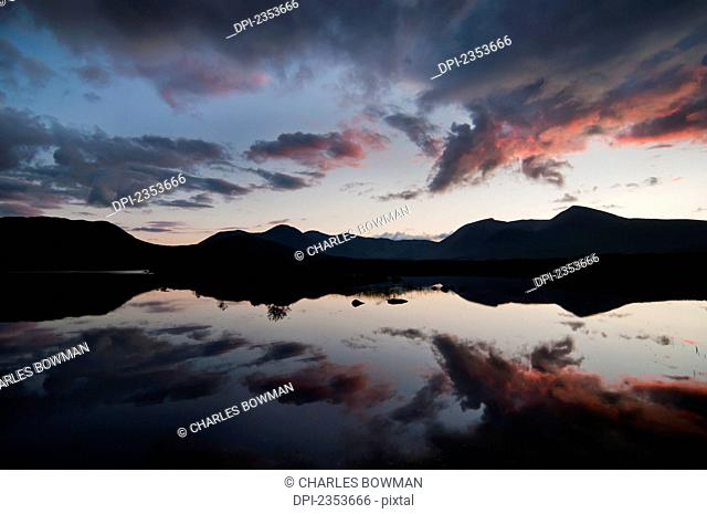 Mirror Image Of Silhouetted Mountains And Clouds At Sunset In A Lake; Rannoch Moor, Scotland