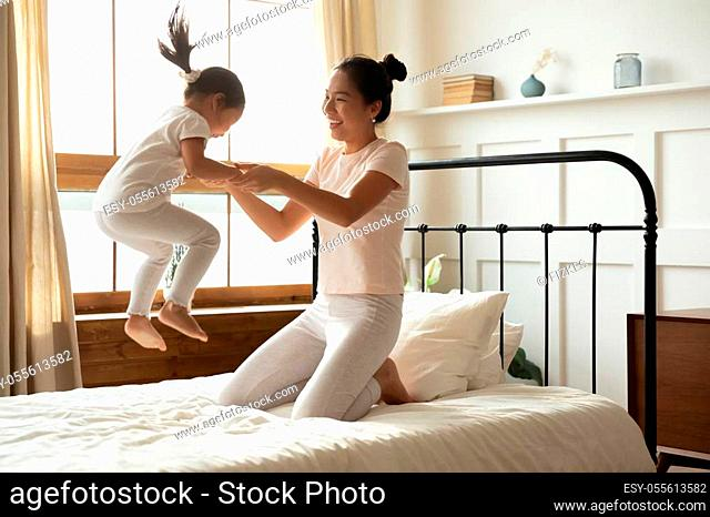 Asian mother holding hands of little toddler daughter while she jumping on bed. Family spend together active energetic funny time in the morning in bedroom