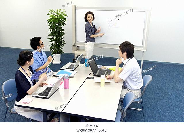 Businessmen and businesswomen in business casual having meeting