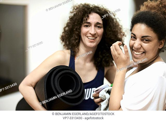 two happy sporty woman laughing in fitness studio