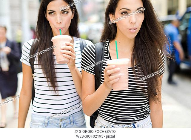 USA, New York City, two twin sisters on the go in Manhattan with takeaway drink