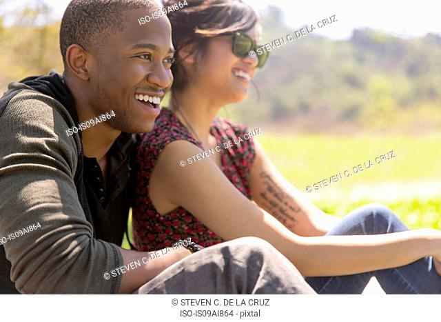 Romantic young couple sitting in rural sunlight
