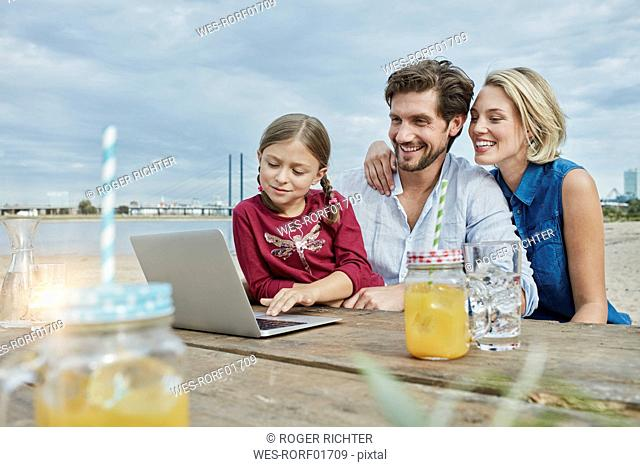 Germany, Duesseldorf, happy family with daughter using laptop on wooden table at Rhine riverbank