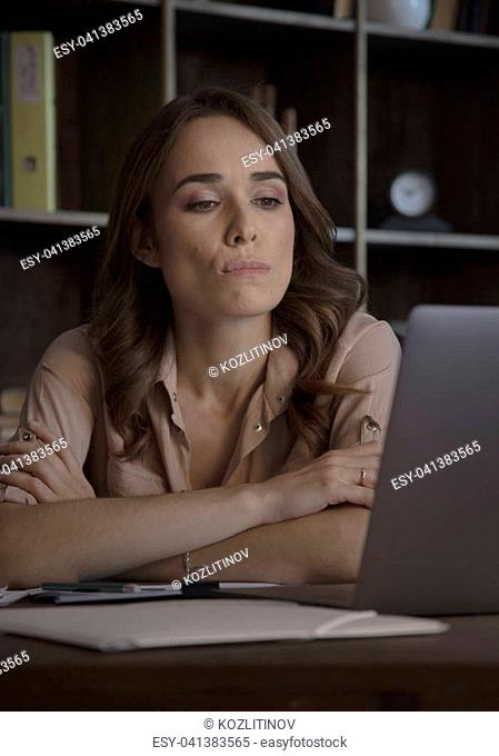 Thoughts in her head. Young beautiful business woman sitting in office at table with gray laptop with pensive expression on face and clasped hands together
