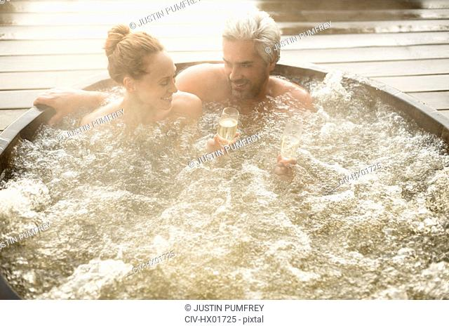 Smiling couple drinking champagne soaking in hot tub on patio