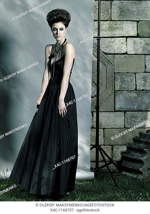 High fashion photo of a beautiful woman wearing long black dress