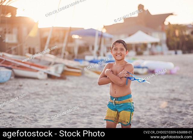 Boy at the beach with arms crossed holding water goggles
