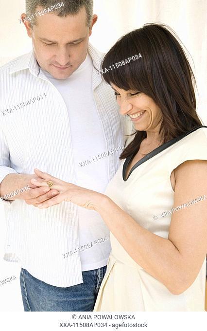 man putting ring on woamns finger