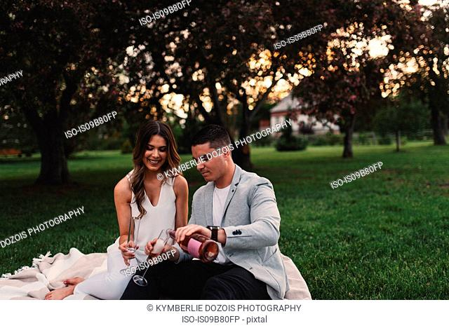 Romantic young couple pouring pink champagne in park at dusk
