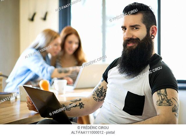Man using laptop computer, smiling, portrait
