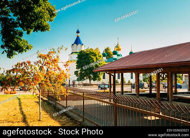 Mir, Belarus. Old Orthodox Church Of The Holy Trinity And Shopping Arcade Or Market In Mir, Belarus. Famous Landmarks In Sunny Autumn Day With Blue Sky