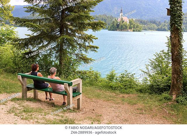 Tourists sitting on a bench on the bank of lake Bled. Church of background