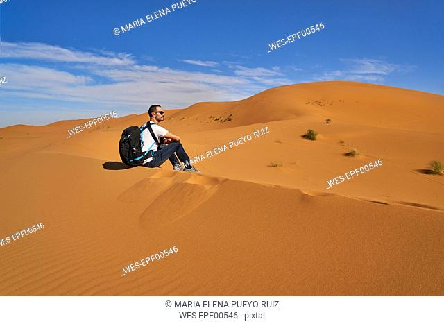 Morocco, man sitting on desert dune looking at view